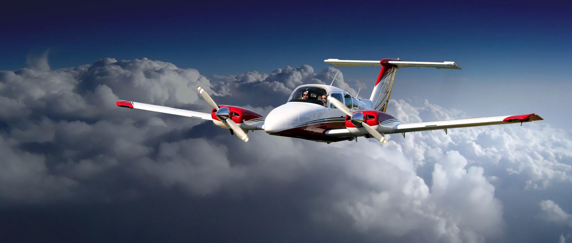 Beechcraft Duchess airplane over clouds